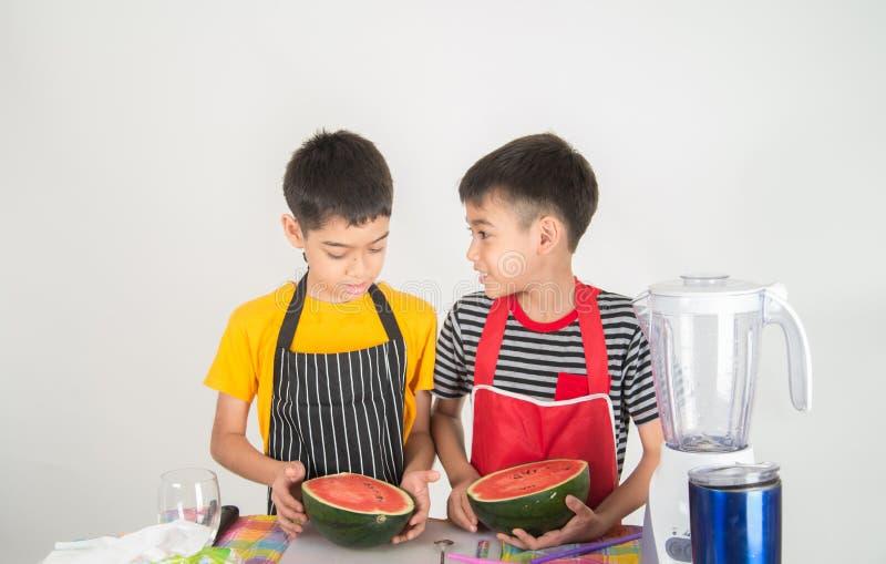 Τα μικρά παιδιά συνδυάζουν το χυμό melone νερού με τη χρησιμοποίηση του σπιτιού μπλέντερ στοκ εικόνες