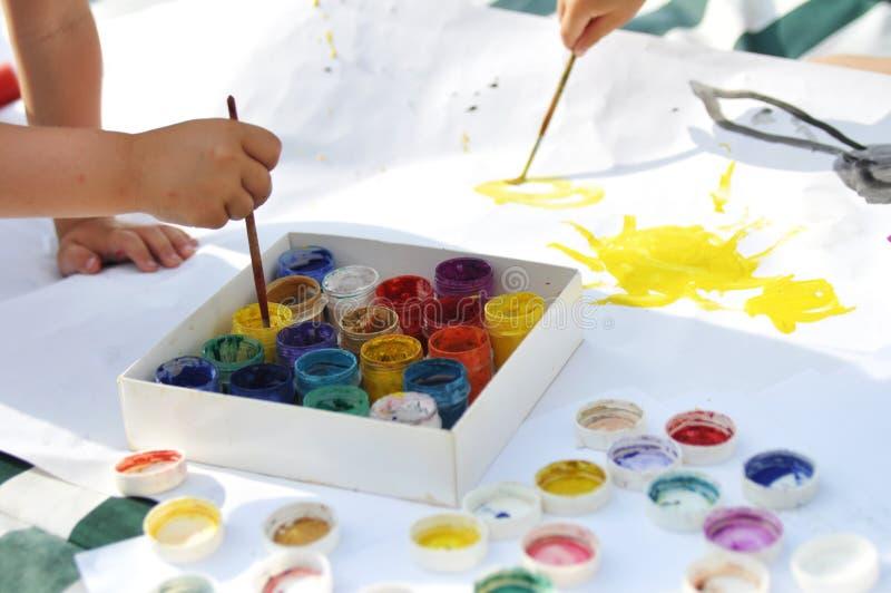 Τα μικρά χέρια παιδιών ` s χρωματίζουν με τα χρώματα και τις βούρτσες σε ένα μεγάλο φύλλο στην οδό μια ηλιόλουστες ημέρα, μια δημ στοκ φωτογραφίες