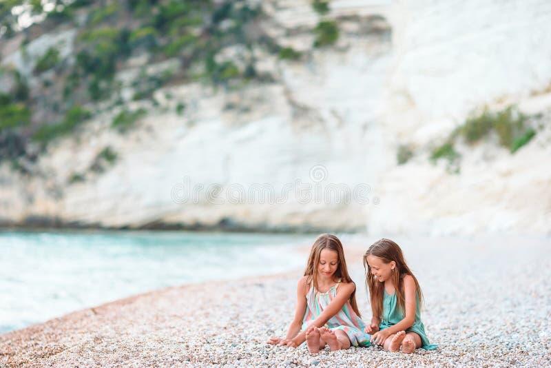 Τα μικρά χαρούμενα αστεία κορίτσια διασκεδάζουν πολύ στην τροπική παραλία παίζοντας μαζί Ηλιόλουστη μέρα με βροχή στη θάλασσα στοκ φωτογραφία