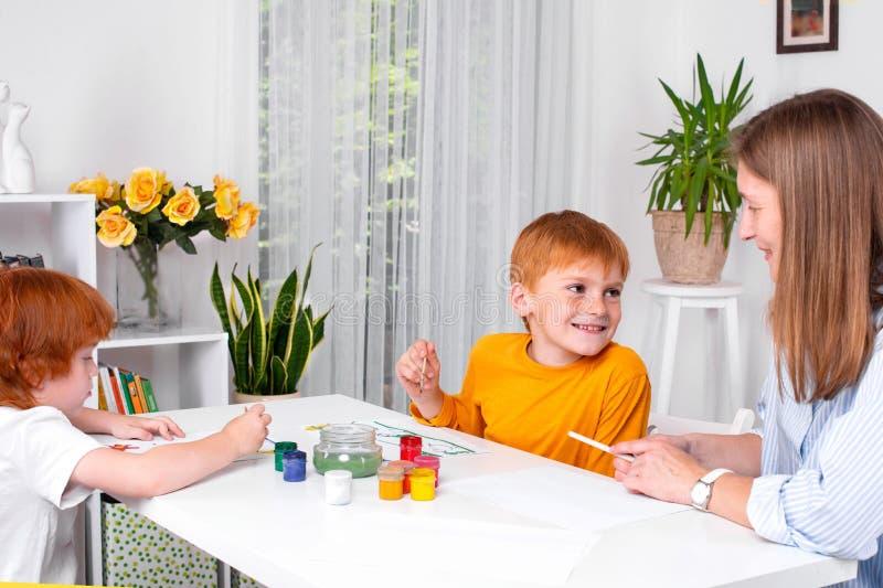 Τα μικρά redhead αγόρια με μια παραμάνα ή μια μητέρα ή το δάσκαλο κάθονται στον πίνακα και το χρώμα με τα χρώματα στοκ εικόνα με δικαίωμα ελεύθερης χρήσης