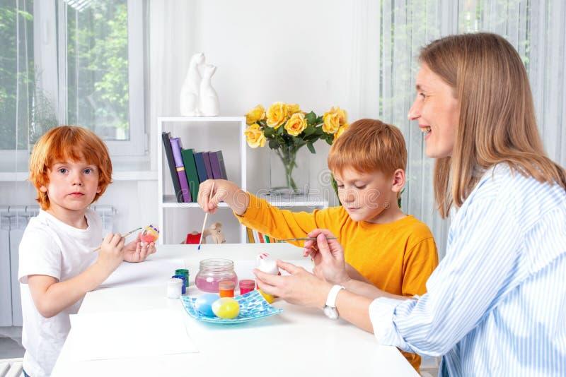 Τα μικρά redhead αγόρια με μια παραμάνα ή μια μητέρα ή το δάσκαλο κάθονται στον πίνακα και το χρώμα με τα χρώματα στοκ εικόνες