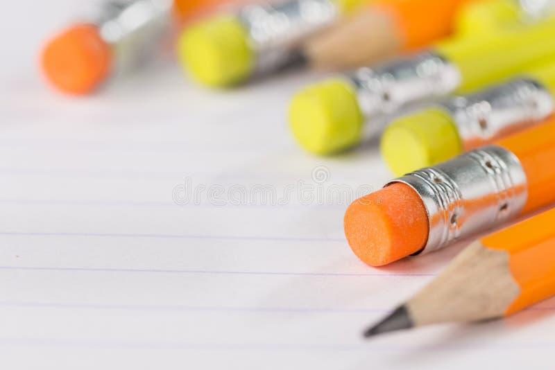 Τα μολύβια με μια γόμα στην πίσω πλευρά βρίσκονται σε ένα φύλλο σημειωματάριων σε μια λουρίδα στοκ φωτογραφίες με δικαίωμα ελεύθερης χρήσης