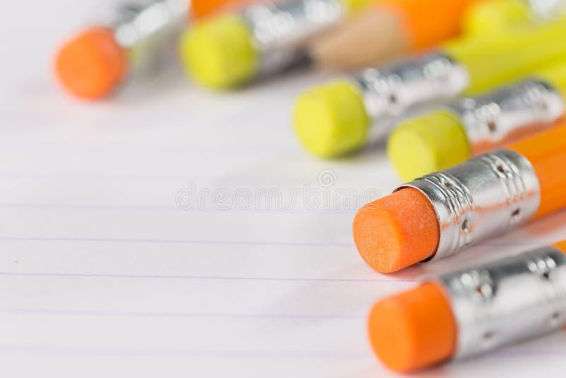 Τα μολύβια με μια γόμα στην πίσω πλευρά βρίσκονται σε ένα φύλλο σημειωματάριων σε μια λουρίδα στοκ φωτογραφίες
