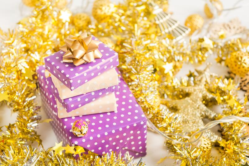Τα μπεζ και ιώδη πορφυρά κιβώτια δώρων παρουσιάζουν το σωρό με την κορδέλλα με τη χρυσή διακόσμηση Χριστουγέννων στοκ εικόνες