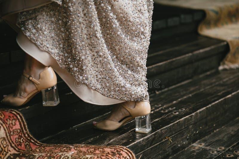 Τα μπεζ παπούτσια με ένα διαφανές τακούνι στα πόδια νυφών ` s πηγαίνουν κατά μήκος της ξύλινης σκάλας, που εξισώνει το φόρεμα με  στοκ φωτογραφία