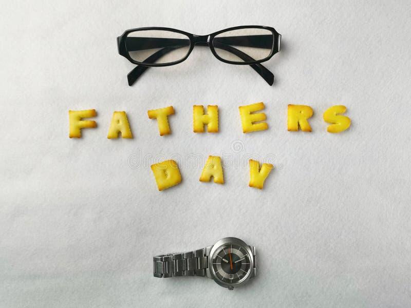 Τα μπισκότα επιστολών, τα γυαλιά και τα ρολόγια μετάλλων τακτοποιούνται σε ένα άσπρο υπόβαθρο για την ημέρα του πατέρα στοκ εικόνες με δικαίωμα ελεύθερης χρήσης