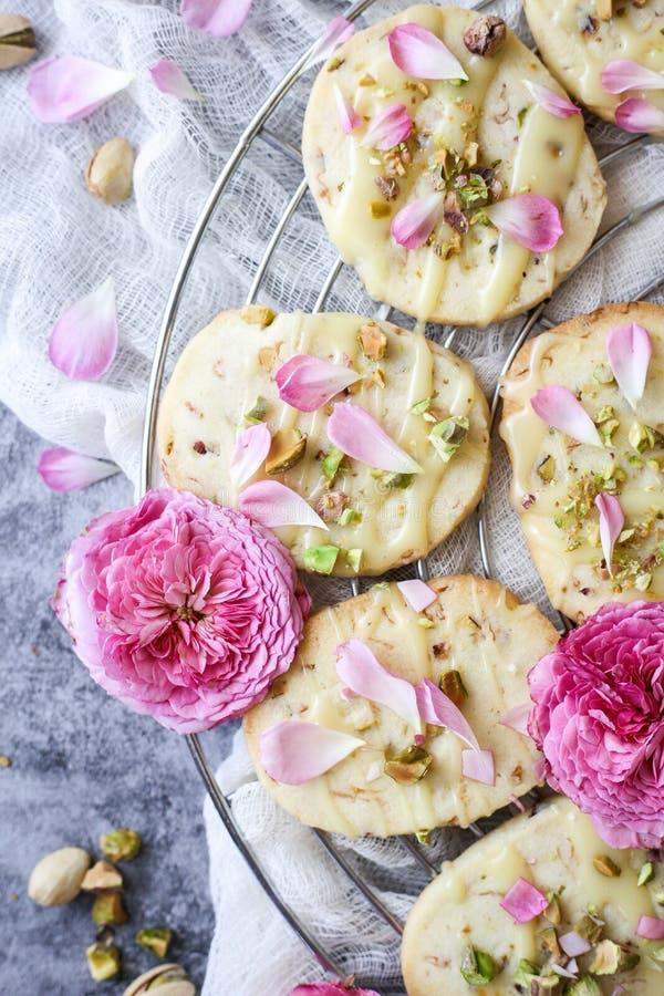 Τα μπισκότα κουλουρακιών με τα φυστίκια και αυξήθηκαν πέταλα στοκ φωτογραφία