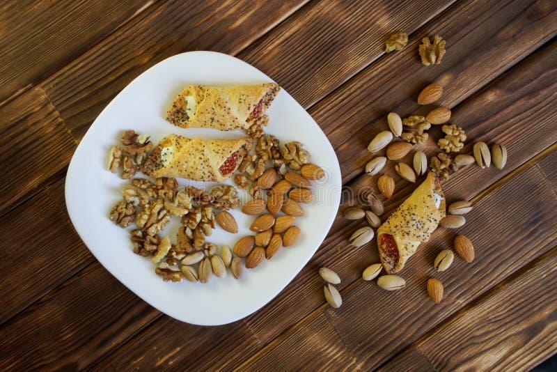 Τα μπισκότα με τη μαρμελάδα, ένα μίγμα φυστικιών, τα ξύλα καρυδιάς και τα αμύγδαλα βρίσκονται σε ένα άσπρο πιάτο σε έναν ξύλινο π στοκ εικόνες
