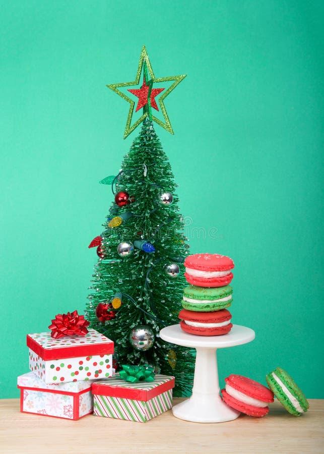 Τα μπισκότα Χριστουγέννων macaron σε ένα μικρό βάθρο με το χριστουγεννιάτικο δέντρο και παρουσιάζουν στοκ εικόνες