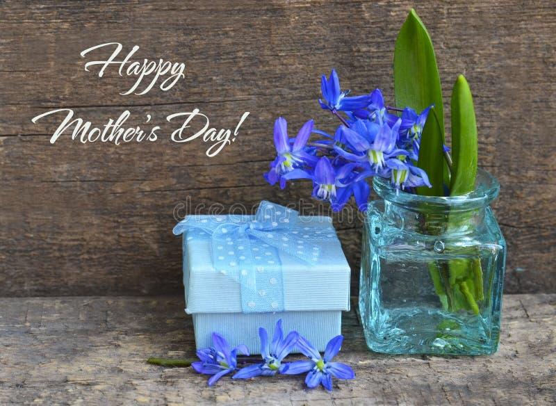 Τα μπλε λουλούδια άνοιξη siberica Scilla σε ένα βάζο γυαλιού με την ημέρα της ευτυχούς μητέρας κολλούν την κάρτα στο παλαιό ξύλιν στοκ φωτογραφία