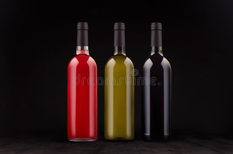 Τα μπουκάλια κρασιού καθορισμένα - κόκκινος, πράσινος, αυξήθηκε - χλευάζουν επάνω στο κομψό σκοτεινό μαύρο ξύλινο υπόβαθρο στοκ φωτογραφίες με δικαίωμα ελεύθερης χρήσης