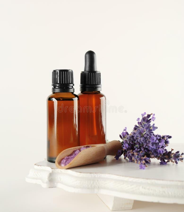 Τα μπουκάλια με το έλαιο αρώματος, το άλας θάλασσας και lavender ανθίζουν στο άσπρο υπόβαθρο στοκ φωτογραφία με δικαίωμα ελεύθερης χρήσης