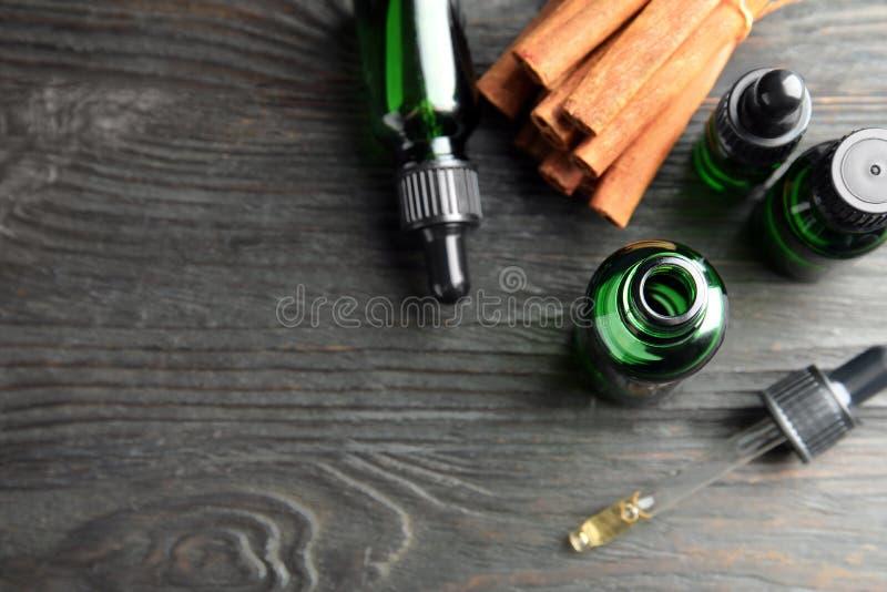 Τα μπουκάλια με το ουσιαστικό πετρέλαιο και τα ραβδιά κανέλας στο μαύρο ξύλινο πίνακα, επίπεδο βάζουν Διάστημα για στοκ φωτογραφία