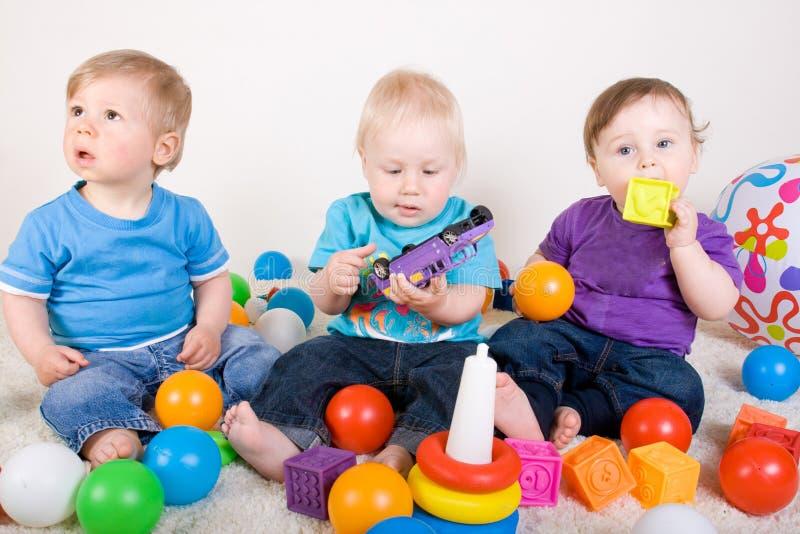 Τα μωρά παίζουν με τα παιχνίδια στοκ φωτογραφίες