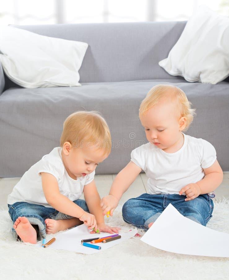 Τα μωρά σύρουν με τα κραγιόνια στο σπίτι στοκ φωτογραφία με δικαίωμα ελεύθερης χρήσης