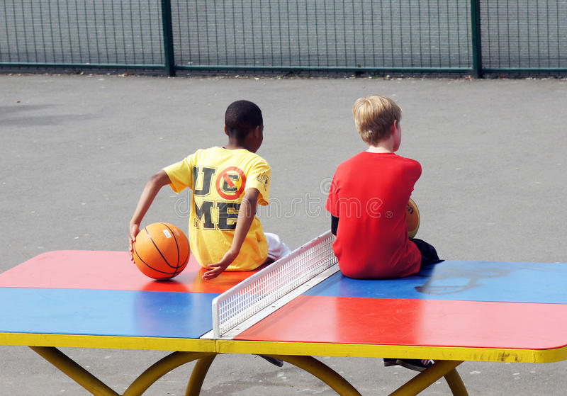 Τα νέα αγόρια κάθονται σε έναν πίνακα επιτραπέζιας αντισφαίρισης στοκ εικόνα με δικαίωμα ελεύθερης χρήσης