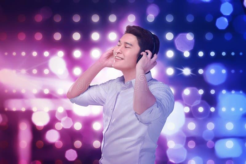 Τα νέα ασιατικά ακουστικά μουσικής ακούσματος ατόμων με χαλαρώνουν στοκ εικόνα με δικαίωμα ελεύθερης χρήσης