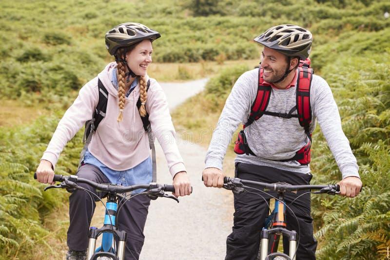 Τα νέα ενήλικα ποδήλατα βουνών ζευγών οδηγώντας σε μια πάροδο χωρών, που φαίνεται μεταξύ τους, κλείνουν επάνω στοκ εικόνες με δικαίωμα ελεύθερης χρήσης