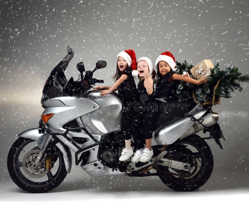 Τα νέα ευτυχή παιδιά κοριτσιών οδηγούν ένα ποδήλατο μοτοσικλετών στο καπέλο santa και το χριστουγεννιάτικο δέντρο στοκ φωτογραφία