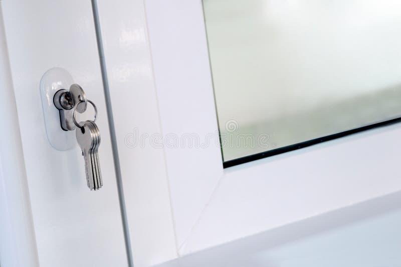 Τα νέα κλειδιά παρεμβάλλονται στην κλειδαριά πορτών δίπλα στο παράθυρο Άνοιγμα ή κλείσιμο μιας άσπρης πλαστικής πόρτας Η έννοια f στοκ εικόνα με δικαίωμα ελεύθερης χρήσης