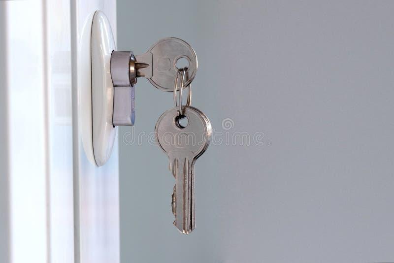 Τα νέα κλειδιά παρεμβάλλονται στη mortise κλειδαριά Άνοιγμα ή κλείσιμο μιας άσπρης πλαστικής πόρτας Η έννοια forgetfulness και τη στοκ εικόνες