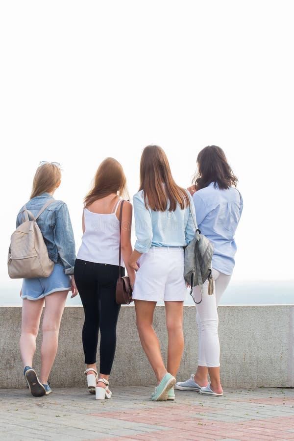 Τα νέα κορίτσια σπουδαστών στέκονται πίσω στη κάμερα και εξετάζουν την απόσταση στην όμορφη φύση στοκ εικόνες