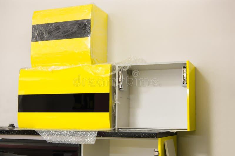 Τα νέα στιλπνά κίτρινος-μαύρα χρώματα επίπλων κουζινών που προετοιμάζονται για συγκεντρώνουν στοκ φωτογραφία