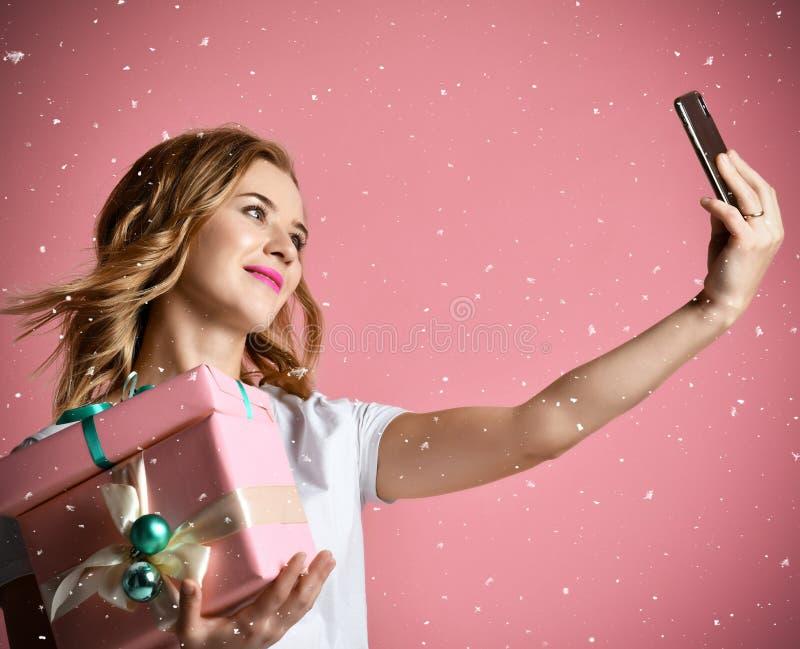 Τα νέα όμορφα δώρα χριστουγεννιάτικων δώρων λαβής γυναικών που χαμογελούν και καθιστούν selfie τη φωτογραφία με το κινητό τηλέφων στοκ φωτογραφία με δικαίωμα ελεύθερης χρήσης
