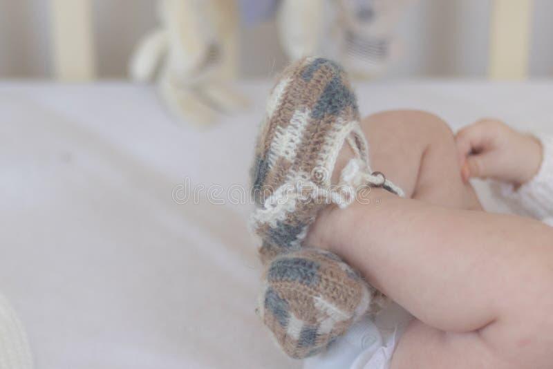 Τα νεογέννητα πόδια μωρών κλείνουν επάνω στις κάλτσες μαλλιού σε ένα άσπρο κάλυμμα Το μωρό είναι στο παχνί Copyspace στοκ εικόνες με δικαίωμα ελεύθερης χρήσης