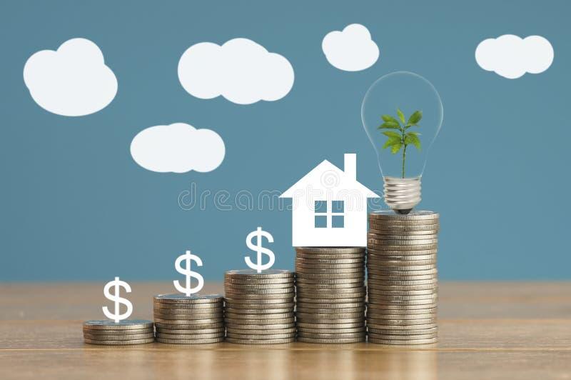 τα νομίσματα και το έγγραφο σπιτιών με το πράσινο μικρό δέντρο, η λάμπα φωτός στα χρήματα, η έννοια μέσα εκτός από, η χρηματοδότη στοκ εικόνα