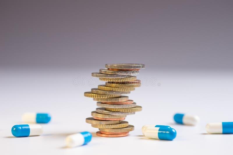 Τα νομίσματα τοποθετούνται μεταξύ τους στις διαφορετικές θέσεις δίπλα στα μπλε και άσπρα χάπια στοκ φωτογραφία με δικαίωμα ελεύθερης χρήσης