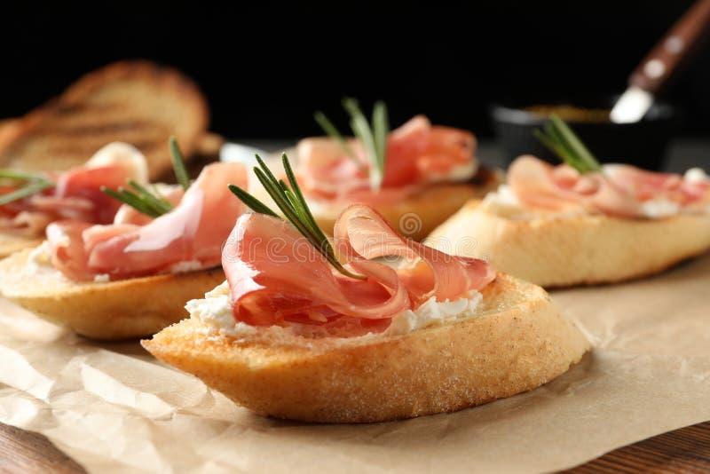 Τα νόστιμα bruschettas με το τυρί prosciutto και κρέμας εξυπηρέτησαν στον πίνακα στο σκοτεινό κλίμα, κινηματογράφηση σε πρώτο πλά στοκ φωτογραφία