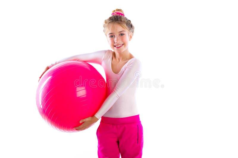 Τα ξανθά κορίτσια παιδιών ικανότητας ασκούν την ελβετική σφαίρα workout στοκ φωτογραφίες