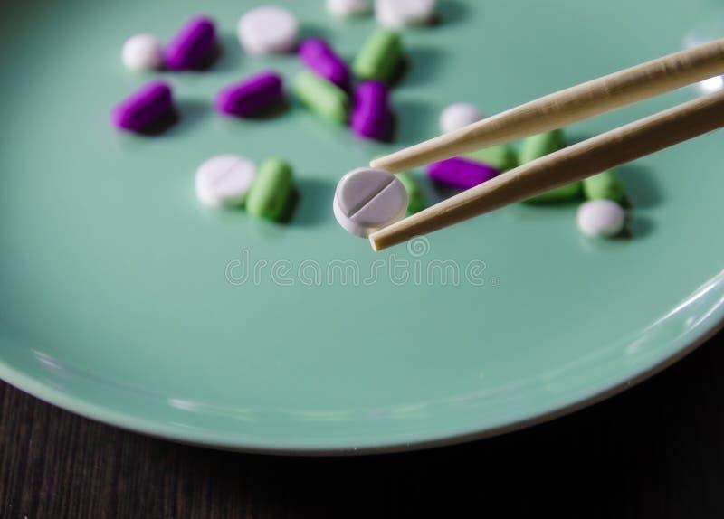 Τα ξυλάκια κρατούν ένα λευκό χάπι στο φόντο των υπολοίπων ξαπλωμένα σε ένα πιάτο που κλείνει στοκ φωτογραφίες με δικαίωμα ελεύθερης χρήσης