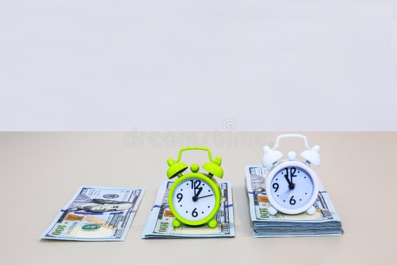 Τα ξυπνητήρια στους σωρούς χρημάτων αμερικανικών δολαρίων αναφέρονται στο χρόνο είναι φράση χρημάτων Έννοια επιχειρήσεων και χρημ στοκ εικόνες