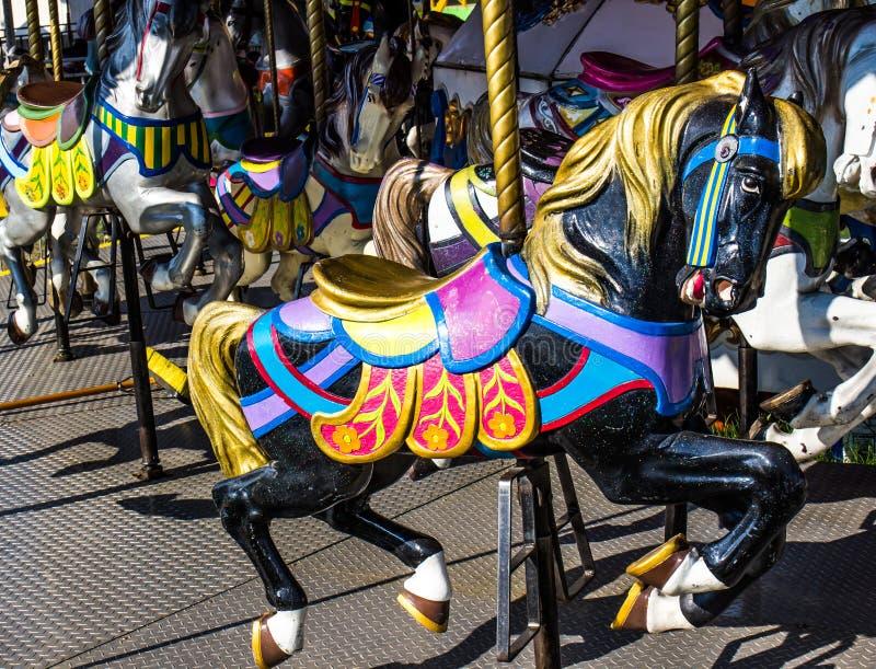 Τα ξύλινα άλογα σε εύθυμο πηγαίνουν γύρω από το ιπποδρόμιο στοκ εικόνες