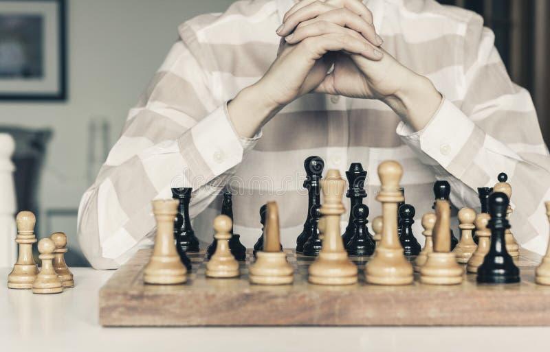 Τα ξύλινα κομμάτια σκακιού σε μια σκακιέρα, παίκτης γυναικών παιχνιδιών σκακιού κάνουν μια κίνηση στοκ φωτογραφία με δικαίωμα ελεύθερης χρήσης