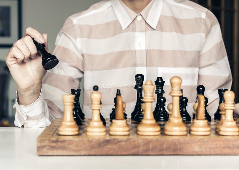 Τα ξύλινα κομμάτια σκακιού σε μια σκακιέρα, παίκτης γυναικών παιχνιδιών σκακιού κάνουν μια κίνηση στοκ εικόνες