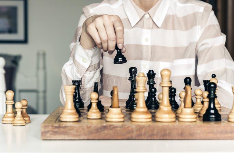 Τα ξύλινα κομμάτια σκακιού σε μια σκακιέρα, παίκτης γυναικών παιχνιδιών σκακιού κάνουν μια κίνηση στοκ φωτογραφία