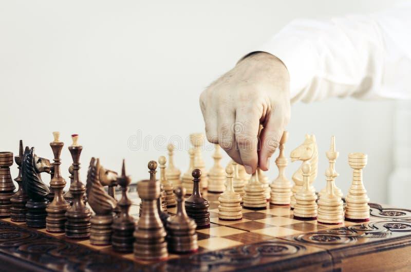 Τα ξύλινα κομμάτια σκακιού σε μια σκακιέρα, παίκτης παιχνιδιών σκακιού κάνουν μια κίνηση στοκ φωτογραφία με δικαίωμα ελεύθερης χρήσης