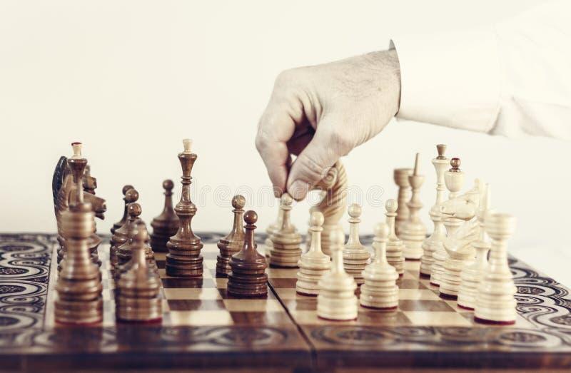 Τα ξύλινα κομμάτια σκακιού σε μια σκακιέρα, παίκτης παιχνιδιών σκακιού κάνουν μια κίνηση στοκ φωτογραφίες με δικαίωμα ελεύθερης χρήσης