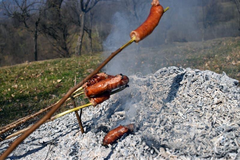 Τα οβελίδια λουκάνικων θερμαίνονται με να ψήσουν στη σχάρα σε μια ειδική αργή πυρκαγιά για πολύ καιρό που τρώει ως οικογενειακό π στοκ φωτογραφία με δικαίωμα ελεύθερης χρήσης