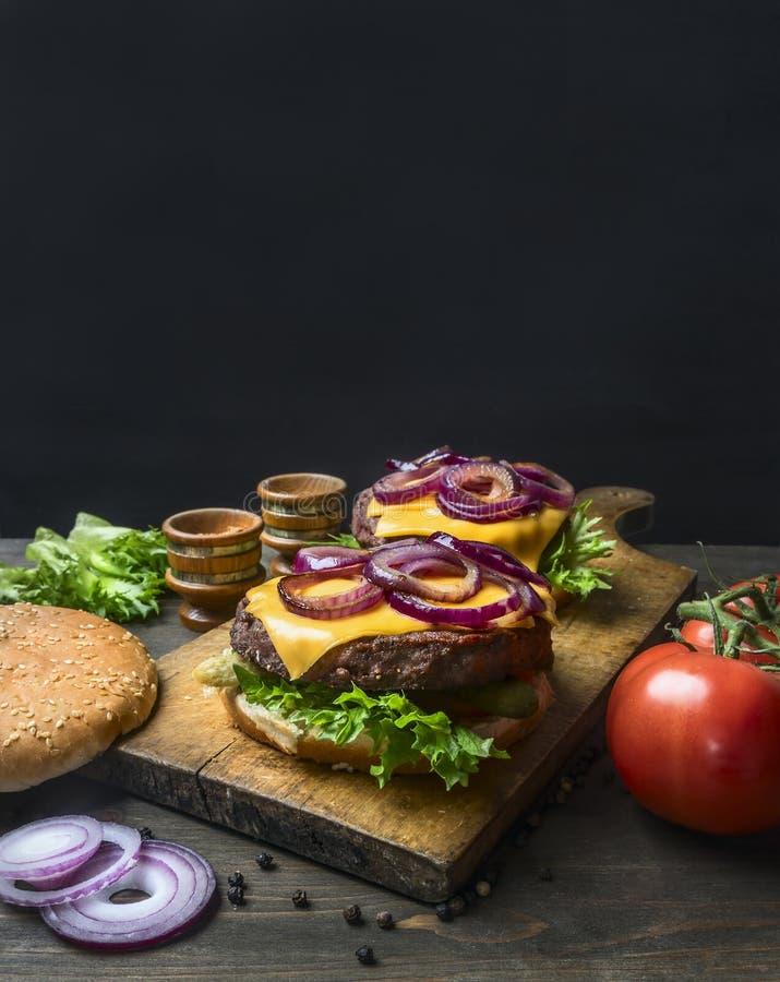 Τα ορεκτικά σπιτικά burgers με μια juicy μπριζόλα βόειου κρέατος, ένα κόκκινο κρεμμύδι, ένα τυρί, μια σαλάτα και τις ντομάτες, στ στοκ εικόνες