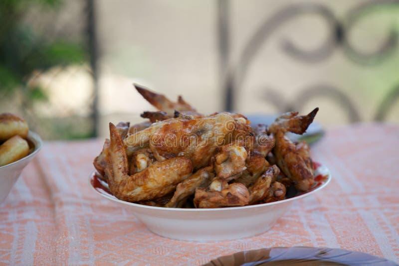 Τα ορεκτικά φτερά κοτόπουλου βρίσκονται στο στρογγυλό πιάτο στοκ εικόνες με δικαίωμα ελεύθερης χρήσης