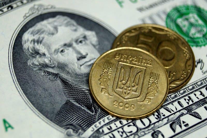 Τα ουκρανικά νομίσματα βρίσκονται σε μια σημείωση σε δύο αμερικανικά δολάρια στοκ εικόνες