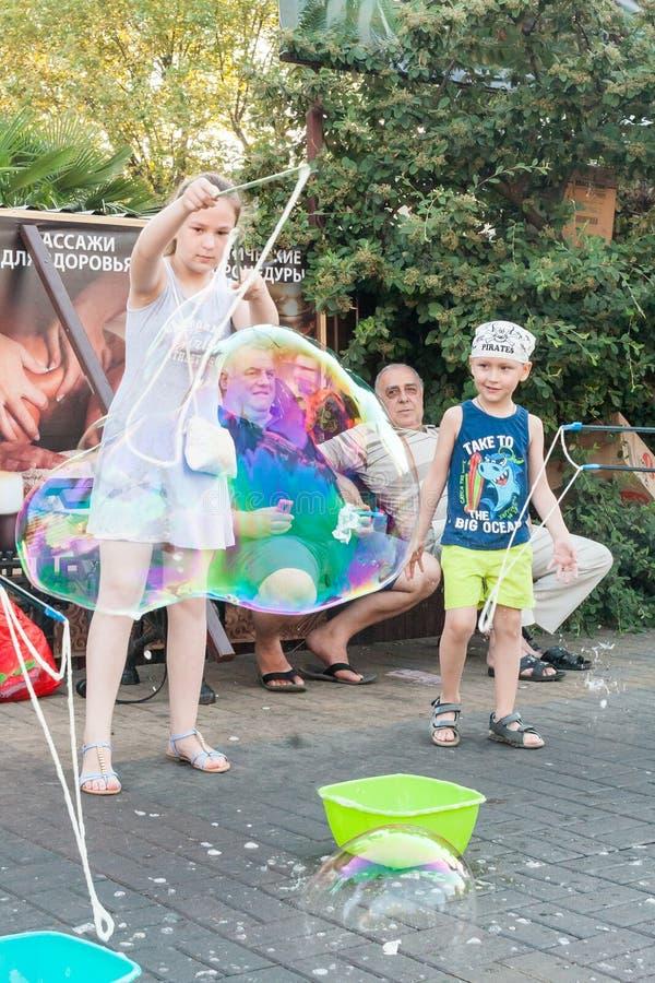 Τα παίζοντας παιδιά ξεκινούν τις φυσαλίδες σαπουνιών στοκ φωτογραφία