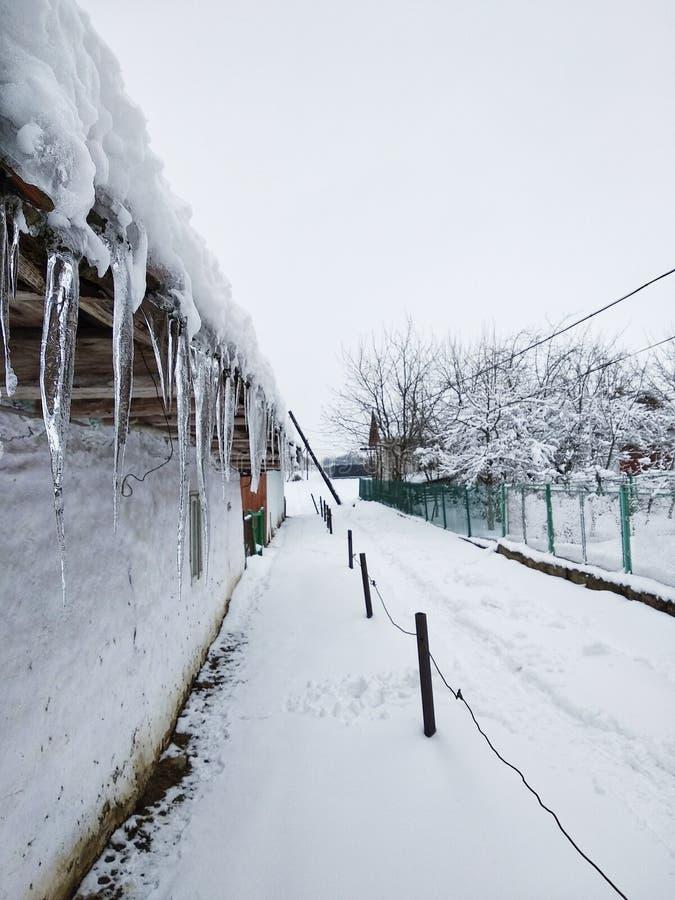 Τα παγάκια που κρεμούν στη στέγη του παλαιού σπιτιού, γη καλύπτονται με το χιόνι, μονοπάτι στο χιόνι Χειμώνας στο ουκρανικό χωριό στοκ φωτογραφίες