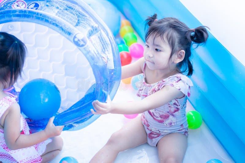 τα παιδιά απολαμβάνουν και έχουν το νερό παιχνιδιού διασκέδασης στη διογκώσιμη λίμνη με ζωηρόχρωμο των μικρών σφαιρών στοκ εικόνα