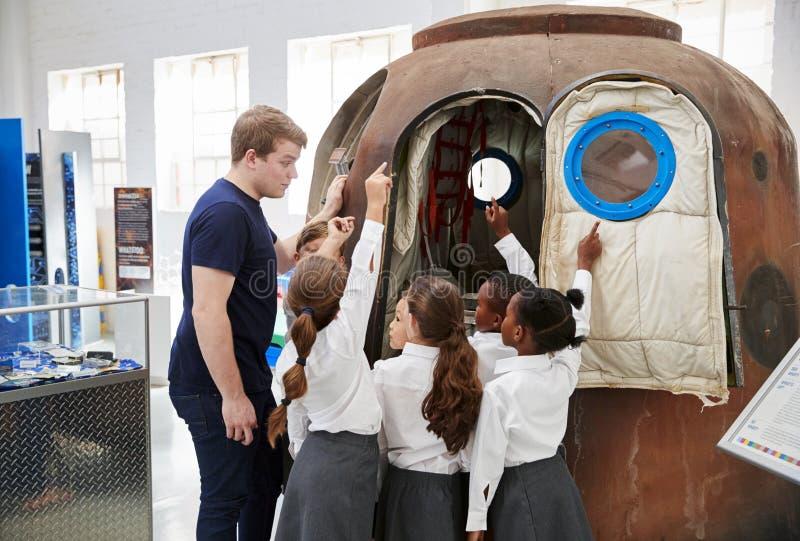 Τα παιδιά και ο δάσκαλος εξετάζουν μια διαστημική κάψα σε ένα κέντρο επιστήμης στοκ φωτογραφίες