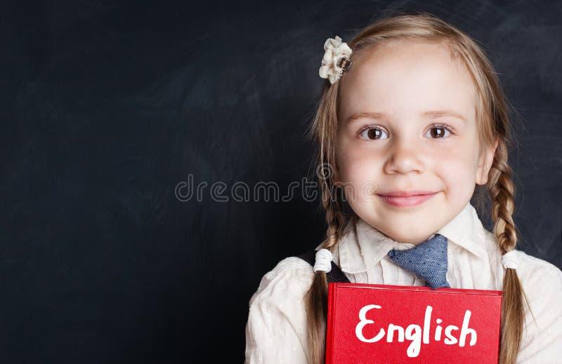 Τα παιδιά μαθαίνουν την αγγλική έννοια Πορτρέτο κινηματογραφήσεων σε πρώτο πλάνο του χαριτωμένου κοριτσιού παιδιών στοκ φωτογραφία με δικαίωμα ελεύθερης χρήσης